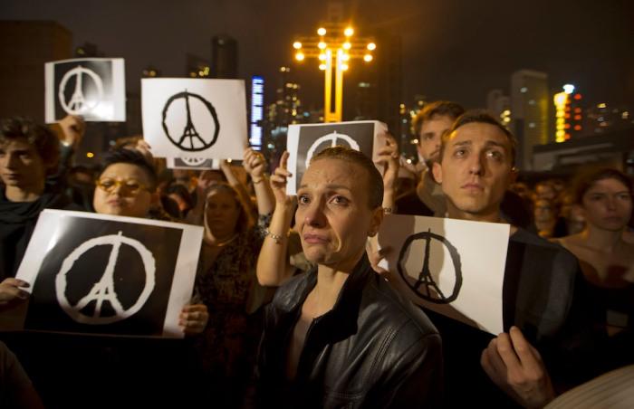 Alcune persone a Hong Kong dopo gli attentati a Parigi (AP Photo/Kin Cheung)