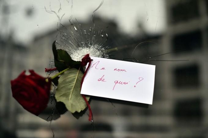 Una rosa e un biglietto lasciati in un foro nella vetrina  di un ristorante a Parigi (LOIC VENANCE/AFP/Getty Images)