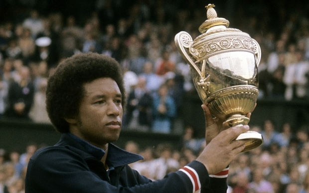 LONDON - JULY 5, 1975: Arthur Ashe of the USA holds up the championship trophy for men's singles of the Wimbledon Lawn Tennis Championships after defeating Jimmy Connors 6-1, 6-1, 5-7, 6-4 July 5, 1975 at the All England Lawn Tennis and Croquet Club in London, England. (Photo by Focus On Sport/Getty Images)